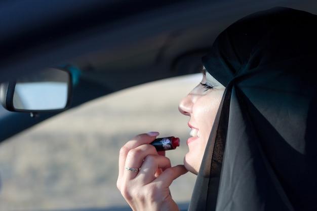 Мусульманская женщина с помадой в машине, традиционной одежде.