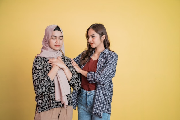 A muslim woman with a panicked gesture and a friend calming her down