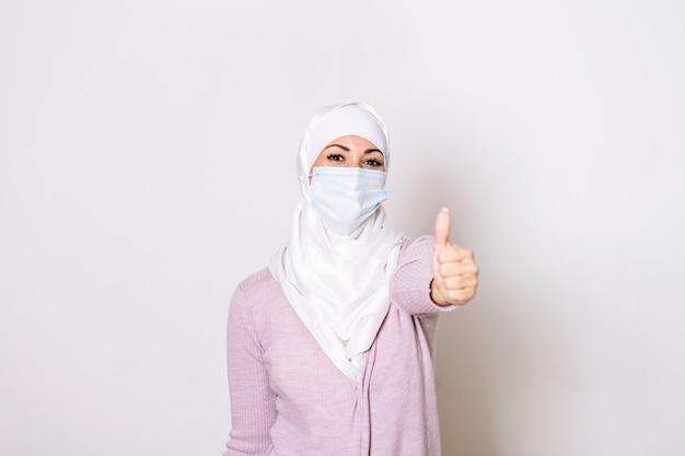 親指を現して防護マスクを持つイスラム教徒の女性。ヒジャーブのフェイスマスクを持つ女性、コロナウイルスの保護