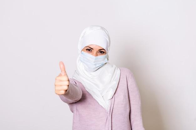 親指を現して防護マスクを持つイスラム教徒の女性。ヒジャーブのフェイスマスクを持つ女性