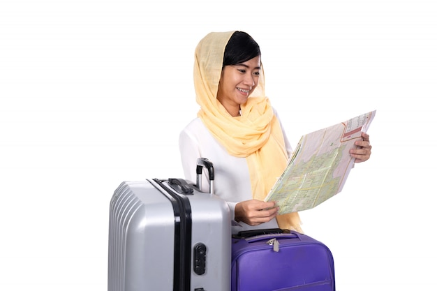Muslim woman with suitcase looking at the map
