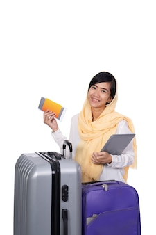 Muslim woman with tablet suitcase and passport over white