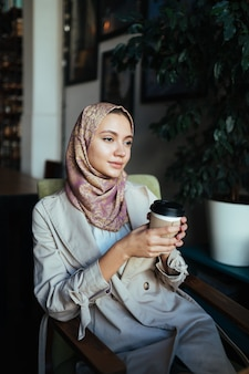 Muslim woman with a thoughtful look sits in a cafe and holds coffee in her hand