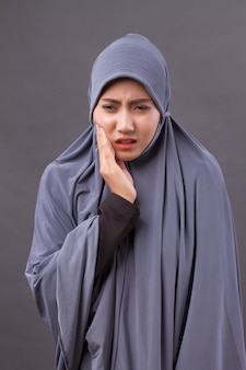 Muslim woman with toothache, tooth decay, sensitivity