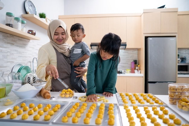 Muslim woman with two her children cooking in the kitchen together making some snack