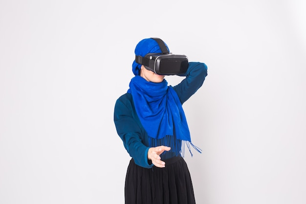 가상 현실 고글을 가진 무슬림 여성. 스튜디오 촬영, 흰색 배경.