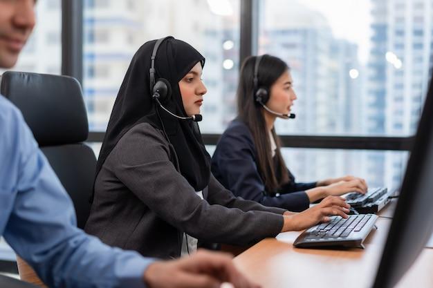イスラム教徒の女性は、コールセンターのコンピューターで作業しているマイクヘッドセットを身に着けているコールセンターのオペレーターとカスタマーサービスエージェントで働いています。