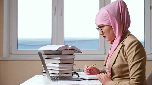 Muslim woman writes with a pen in a notebook looking into a laptop