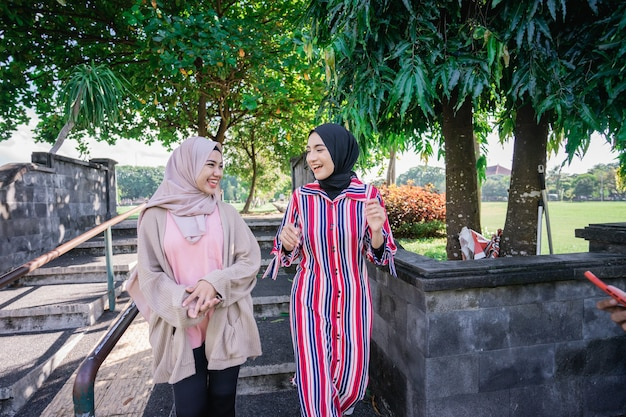 Muslim women in hijabs outdoors on sunny day with friend happy and laugh while walking outdoor