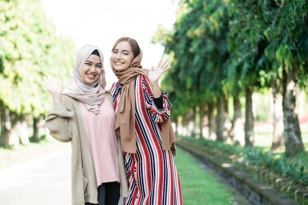 Muslim women in hijabs outdoors on sunny day with friend happy wave their hand to camera