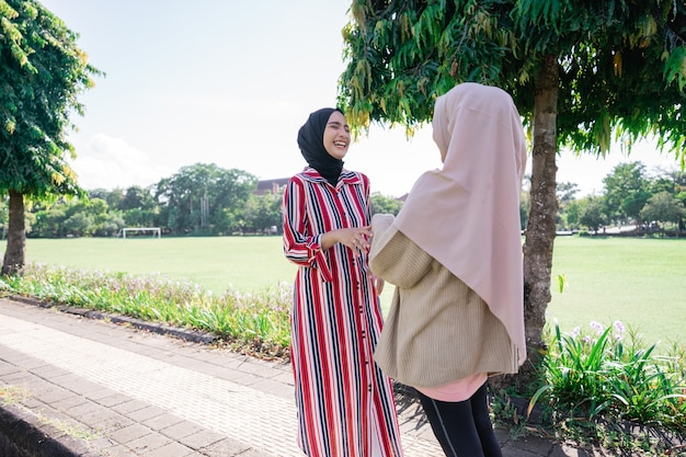 Muslim women in hijabs outdoors on sunny day with friend happy