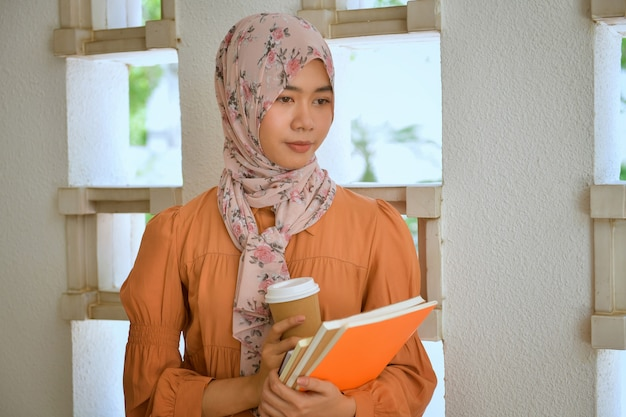 Мусульманские женщины держат файлы и держат чашку кофе во время обеденного перерыва.