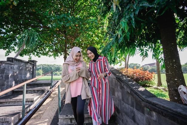 晴れた日に屋外でヒジャーブのイスラム教徒の女性は、屋外を歩きながら幸せで笑う友人と