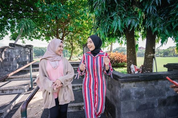 화창한 날 야외에서 히잡을 쓴 이슬람 여성들이 친구와 함께 행복하고 야외에서 걷는 동안 웃는다