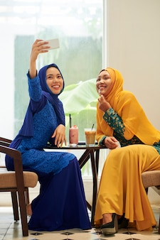 Muslim women photographing in cafe