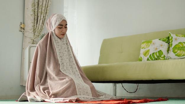 무케나를 입고 두 절 사이에 앉아 기도하는 이슬람 여성