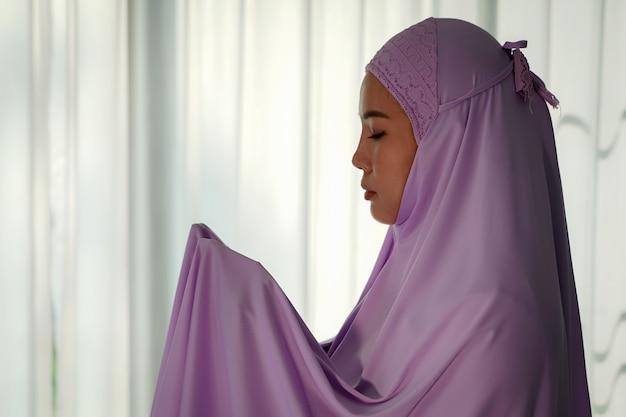 コロナウイルス(covid-19)の発生時に家のロビーで祈るイスラム教徒の女性、検疫の概念。