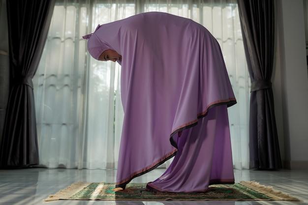 코로나바이러스(covid-19)가 발생하는 동안 집 로비에서 기도하는 이슬람 여성, 검역 개념.