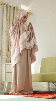 무케나를 입고 기도하는 이슬람 여성