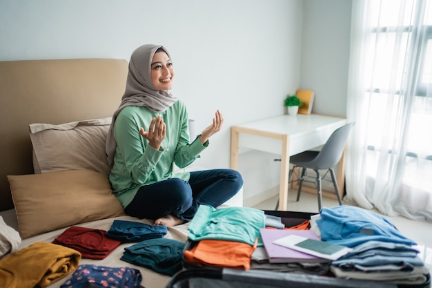 Мусульманские женщины молятся с кроватью, полной одежды