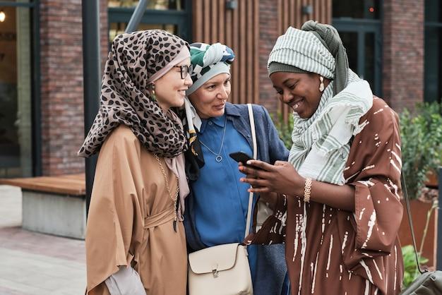 친구와 통화하는 동안 전화로 메시지를 읽고 야외에서 회의하는 동안 웃는 이슬람 여성