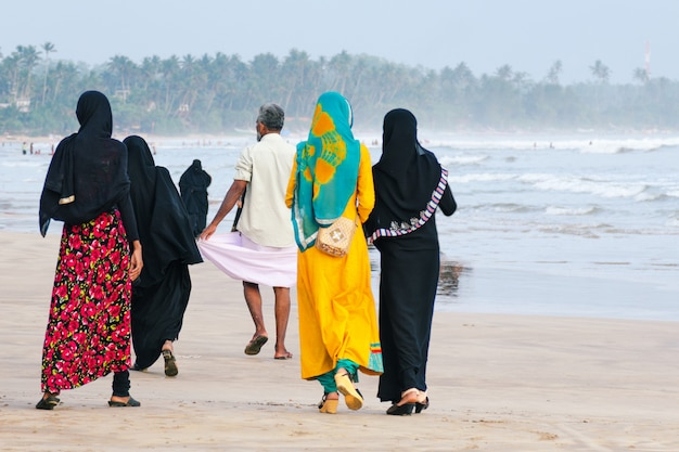 Muslim women walk along the beach, a man walks ahead.