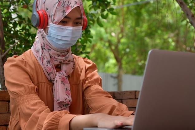 이슬람 여성들은 마스크를 쓰고 헤드폰을 사용하여 노트북에서 음악을 듣습니다. 19 코로나 바이러스 전염병 동안 휴식을 취하기 위해 사회적 거리를 유지하는 개념