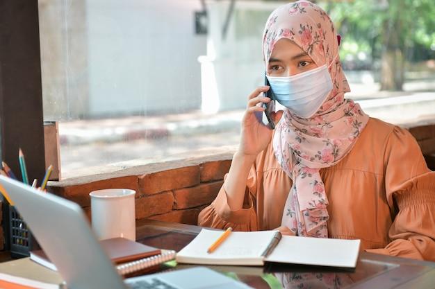 이슬람 여성들은 마스크를 쓰고 집에서 친구들과 대화를 나누기 위해 전화를 사용합니다. covid 19 전염병 동안 사회적 거리를 유지하는 개념