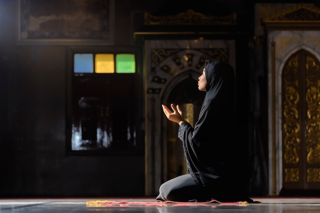 Muslim women wearing black shirts doing prayer according to the principles of islam.
