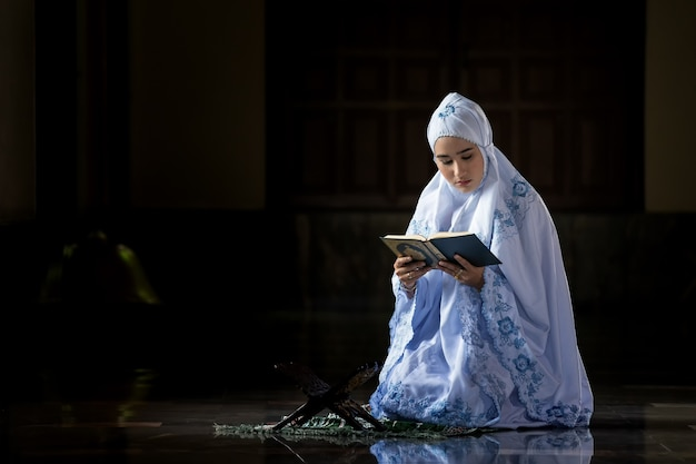 Muslim women wearing white shirts doing prayer according to the principles of islam.