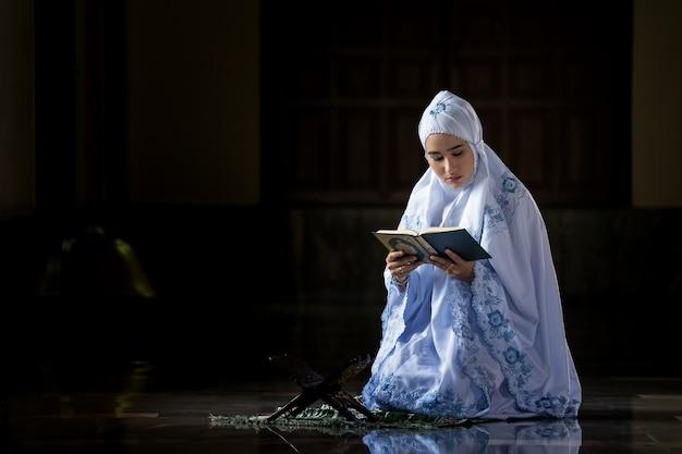 Muslim women wearing white shirts doing prayer according to the principles of islam.