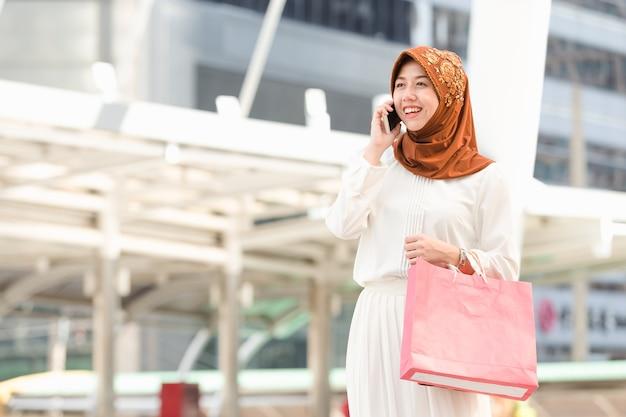 Мусульманская девушка звонит по телефону очень доволен покупками в городе, концепция шоппинга