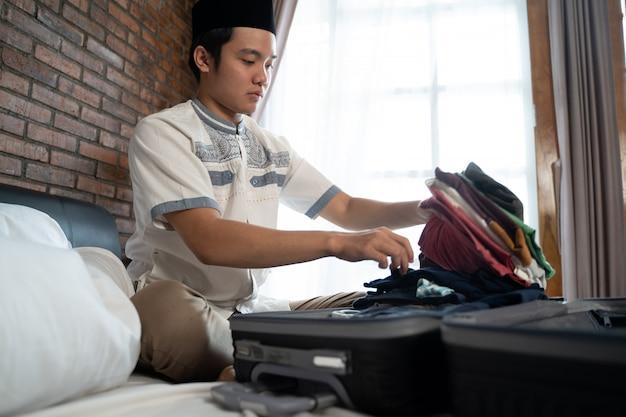 イスラム教徒の若い男の準備と服の梱包