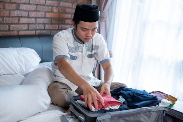 Muslim young man preparing and packing clothes