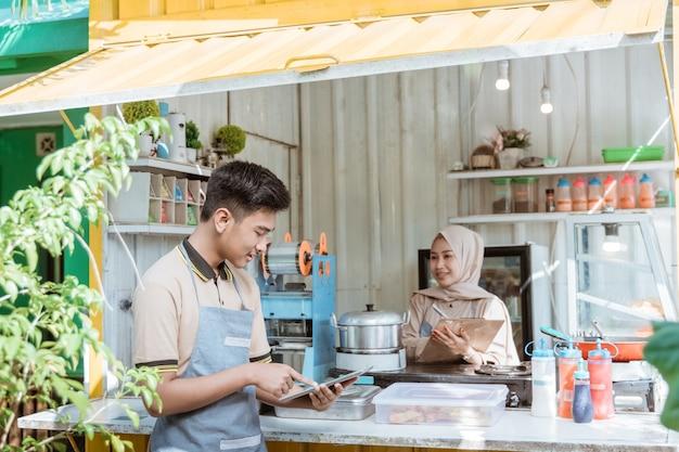 販売について何かを話しているイスラム教徒の若い男性と女性