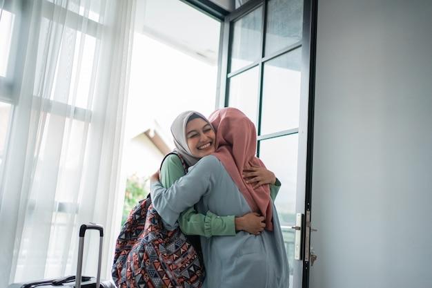 Мусульманская молодая женщина обнимает друга