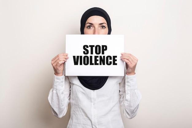 ヒジャーブのイスラム教徒の若い女性は、「stopviolence」というテキストのバナーで顔を覆っています。