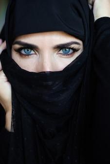 검은 히잡을 쓰고 어두운 배경에 이슬람 젊은 여성