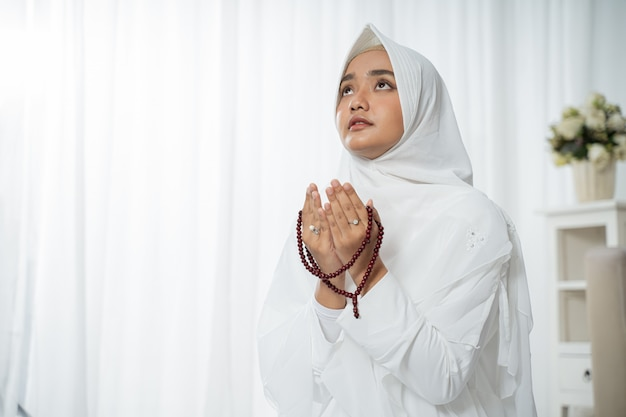 Muslim young woman praying in white traditional clothes