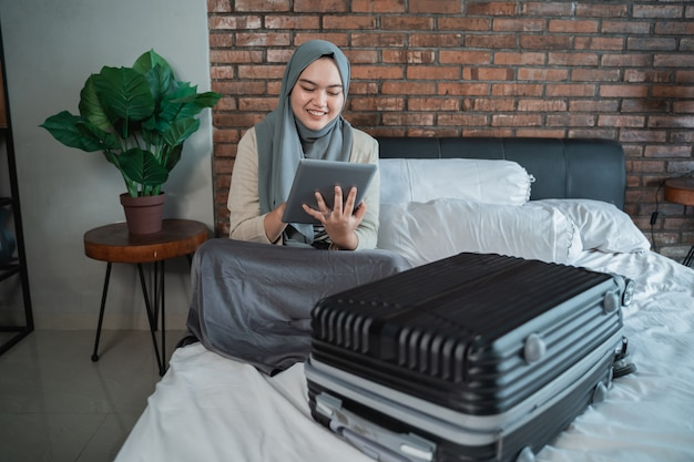 Muslim young woman using tablet with full suitcase