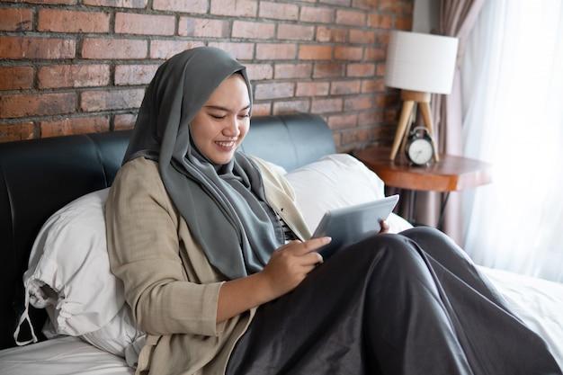 태블릿을 사용 하여 이슬람 젊은 여자