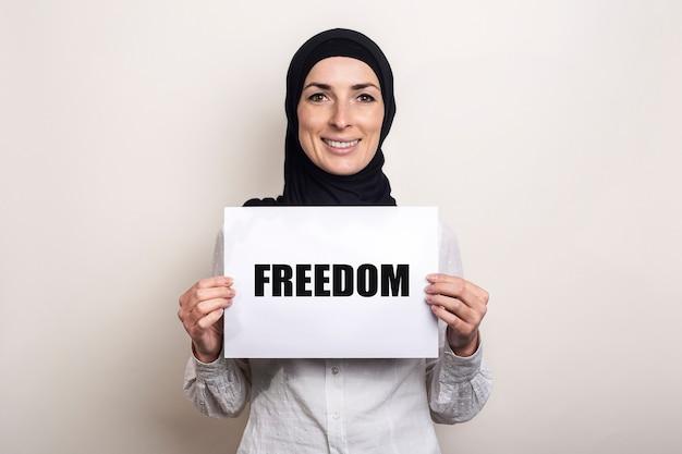ヒジャーブで笑顔のイスラム教徒の若い女性は、テキストfreedomのバナーを保持しています