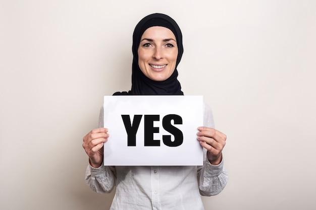 ヒジャーブで笑顔のイスラム教徒の若い女性は、テキストyesのバナーを保持します