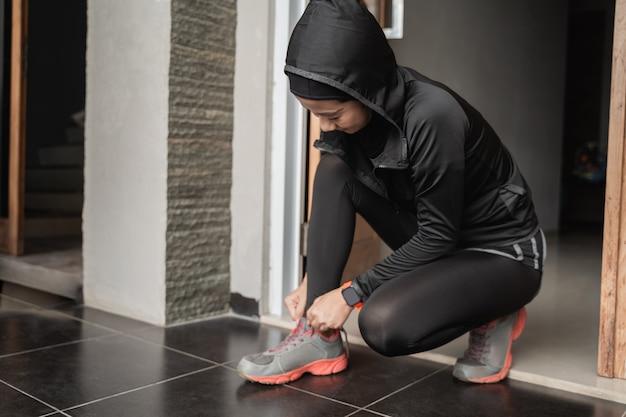 イスラム教徒の若い女性がスポーツヒジャーブを着用し、ドアで靴ひもを修理する