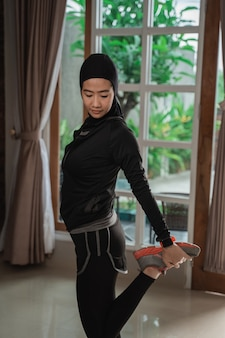 ストレッチを行うヒジャーブスポーツウェアを着ているイスラム教徒の若い女性