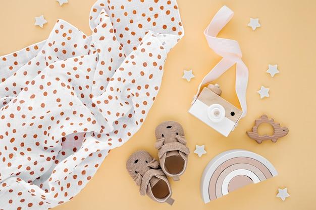 Пеленальное одеяло из муслина с детскими тапочками и игрушками на желтом фоне. набор гендерно-нейтральных аксессуаров для новорожденных. плоская планировка, вид сверху
