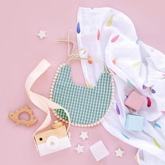 Пеленальное одеяло из муслина с нагрудником и детскими игрушками на розовом фоне. набор вещей и аксессуаров для новорожденных. плоская планировка, вид сверху