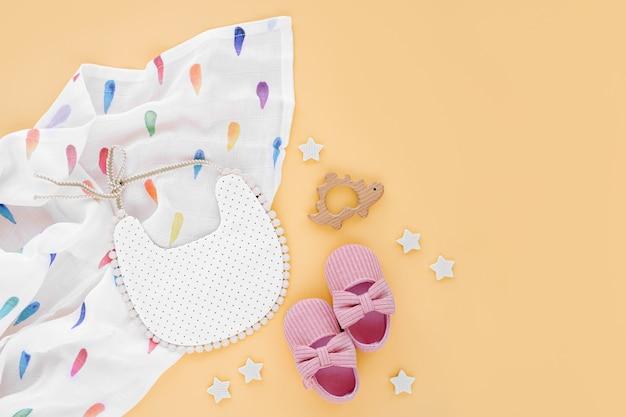 노란색 배경에 턱받이, 신발, 아기 장난감이 있는 모슬린 포대기 담요. 신생아를 위한 물건과 액세서리 세트. 평평한 평지, 평면도