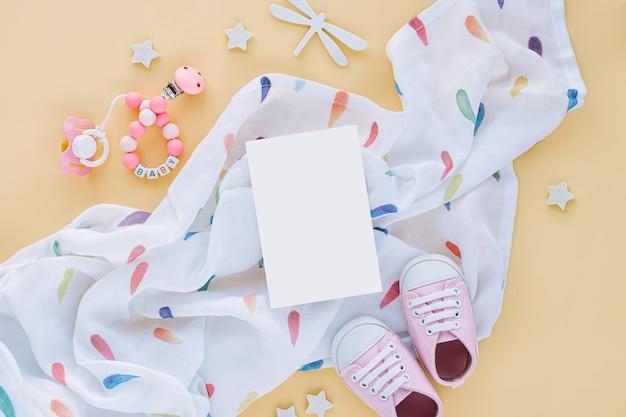 Муслиновое пеленание с пустой карточкой и детские тапочки, игрушки на желтом фоне. макет текста. набор аксессуаров для новорожденных. плоская планировка, вид сверху
