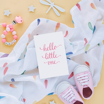 Одеяло пеленать муслина с карточкой здравствуйте! тапочки малыша и младенца, игрушки на желтой предпосылке. набор аксессуаров для новорожденных. плоская планировка, вид сверху
